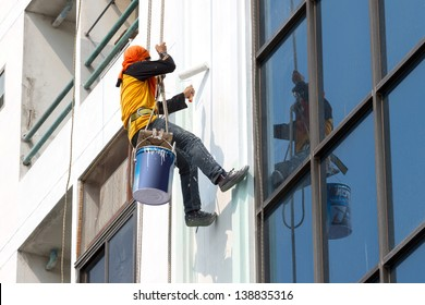 Painters are painting buildings.