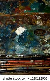 Painter's palette and brushes, old materiel covered with oil painting