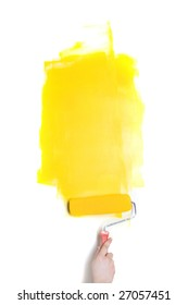 Paintig roller with yellow paint in human hand