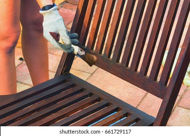 Painting and applying protective varnish on a wooden garden chair