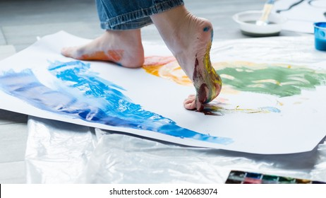 Painting art school. Closeup of artist feet walking on paper, creating colorful abstract artwork.