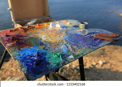 Painting artist with oil painting on nature. Brush and palette