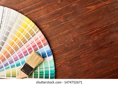 Painting brush and color guide palette on wooden table with place for text.