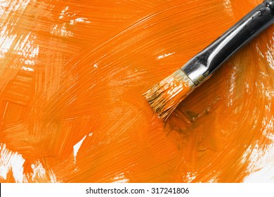 Painting brush and orange paint as a background