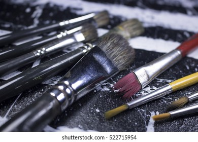 painting brushes on black and white paint color canvas