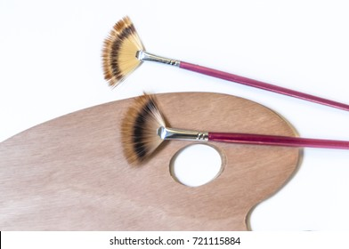 Painting brushes and palette isolated on white background. waiting for the artist, unused painting brushes and palette. Artists palette