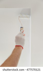 Painting the ceiling and walls. Hand holding a roller.