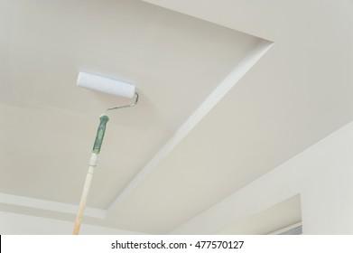 Deckenmalerei und Wände. Roller, der die Oberfläche berührt und einen Farbverlauf hinterlässt.