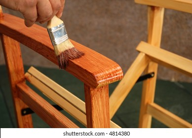 painting a chair with a brush