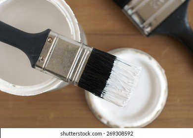 Painting and decorating shallow focus top down view of a pot of white paint and brush
