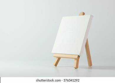 Painting easel with empty canvas on white background