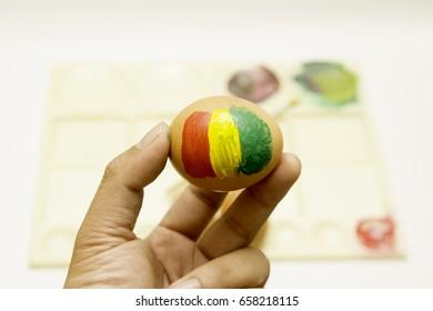 Painting easter eggs, egg painting stripes Jamaica, reggae