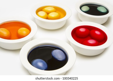 Painting easter eggs with liquid colour in white bowls