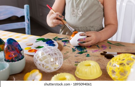 Painting easter eggs as a traditional homemade craftby little child. Colorful decorative eggs on a table with hands of kid. Close up