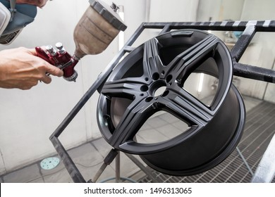 Painting the element body of the car - the aluminum alloy wheel with the help of aerograf in black color by the hand of painter repairman in the industrial professional garage. Auto service industry.