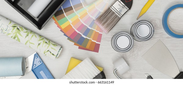 Painting equipment, paint swatches, and rolls of wall paper shot overhead over white wooden background