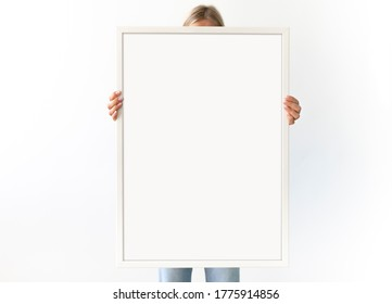 Painting frame mockup. Woman holds a big vertical white picture frame. Copy space for your logo