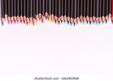 Painting multicolored border from colorful pencils for art creativity on a white background. Flat lay
