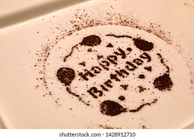 A painting on a white plate for celebrating birthday with cocoa or chocolate powder. Food display and decoration.