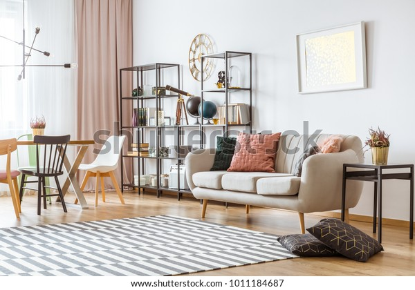 Painting on white wall above sofa with cushions in living room interior with chairs at the table under metal lamp