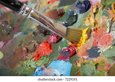Painting paintbrush on colorful painting palette. Shallow DOF.