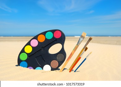 Painting palet and brushes at the beach
