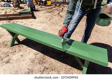 Painting a picnic bench green.