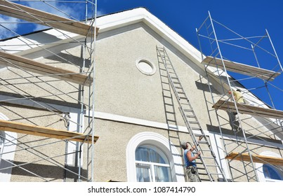 Painting and plastering exterior house scaffolding wall. Home facade insulation, sctucco and painting works during exterior wall  renovations and repair. Contractors plastering house facade outdoor