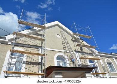 Painting and Plastering Exterior House Scaffolding Wall. Home Facade Insulation, Stucco and Painting Works During Exterior Wall  Renovations and Repair. Builder Worker Plastering House Facade Outdoor
