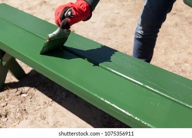 Painting a public park picnic bench.