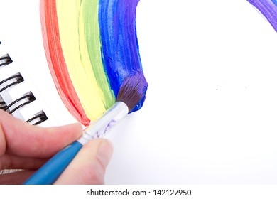 Painting of rainbow on notebook or sketch book with paintbrush, close-up