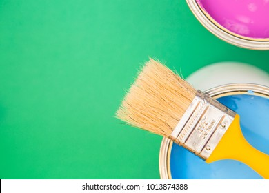 Painting, Redecorating House Concept. Tin can of blue oil paint with a brush, green background with copy space, top view, flat lay