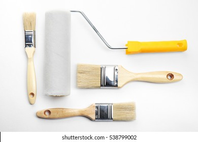 Painting roller and brushes on white textured background