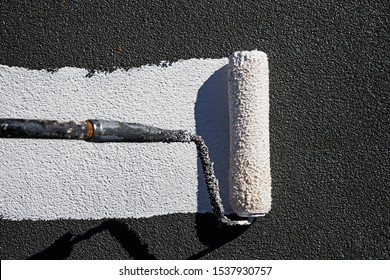 painting a roof with reflective white elastomeric coating with a paint roller
