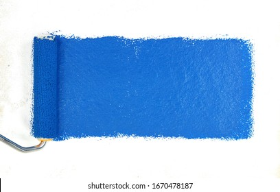 Painting a rough wall with roller. Paint roller leaving stroke of white color over a rustic background. usable for text and messages. Blue background.