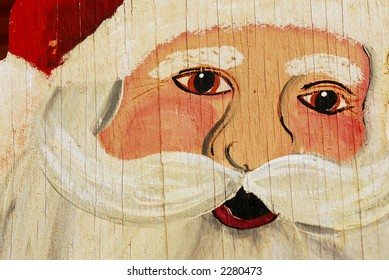 A painting of Santa on plywood.  It is aged and weathered with cracks and peeling paint.
