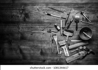 painting still life with lot of type brushes and other tools on a wooden background