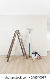 Painting supplies with ladder against a wall to be repainted