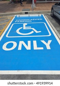 Painting symbol or sign white and blue color for  Handicapped reserved parking only on street or road.