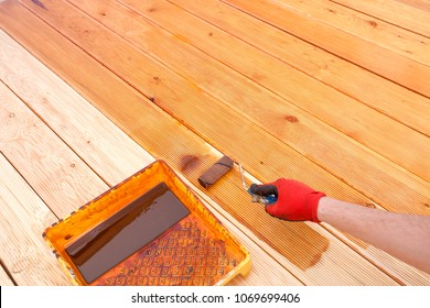Painting a terrace board impregnation water proofing. Carpenter painting wood.