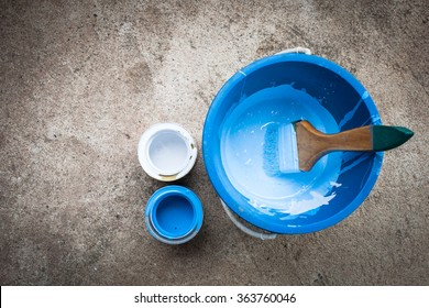 painting tool with color in bucket on floor