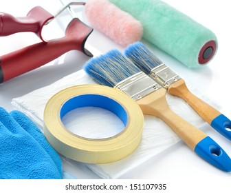 Painting tools on white background. Paint rollers, brushes, drop cloth, masking tape and gloves.
