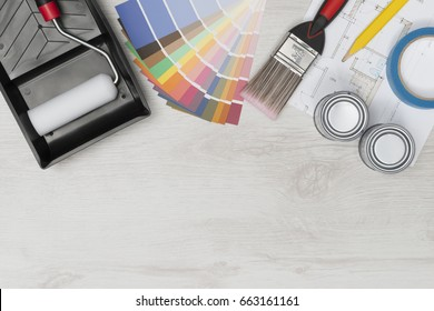 Painting tools and supplies including brush, roller, tray, and paint swatches plus an architectural blueprint on white wooden surface with copy space