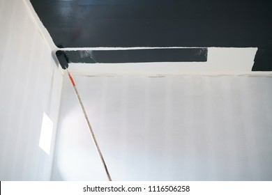 Painting wall ceiling with black color by roller