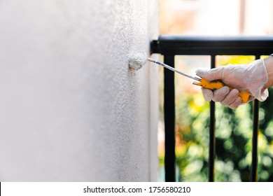 Painting the wall of the house terrace white. Concept of painting and reforming the house.