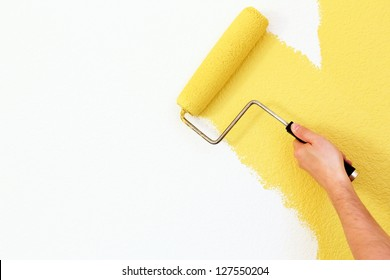painting a wall with roller close-up on hand