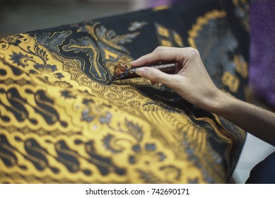 Painting watercolor on the fabric to make Batik
