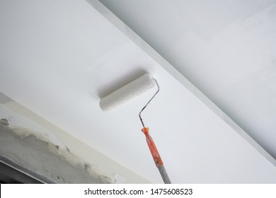 painting a white gypsum plaster ceiling with paint roller