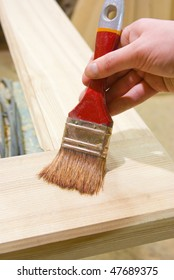 painting wood plank with brush