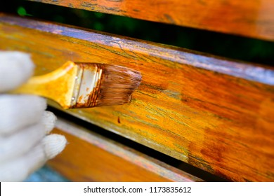 painting a wooden fence - a brush close-up, a very shallow depth of field